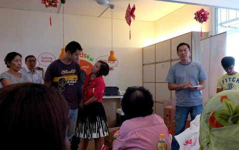 Outreach worker Erwin, in gray, briefs volunteers on a house visit activity.